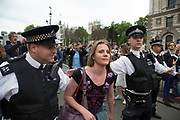 London, UK. Wednesday 27th May 2015. Young protester plays gently with police as students demonstrate in Westminster against Tory Party cuts. The protest was focussed on a number of subjects including spending cuts but generally was a mark of displeasure and concern as to what the Conservatives will do while in power.