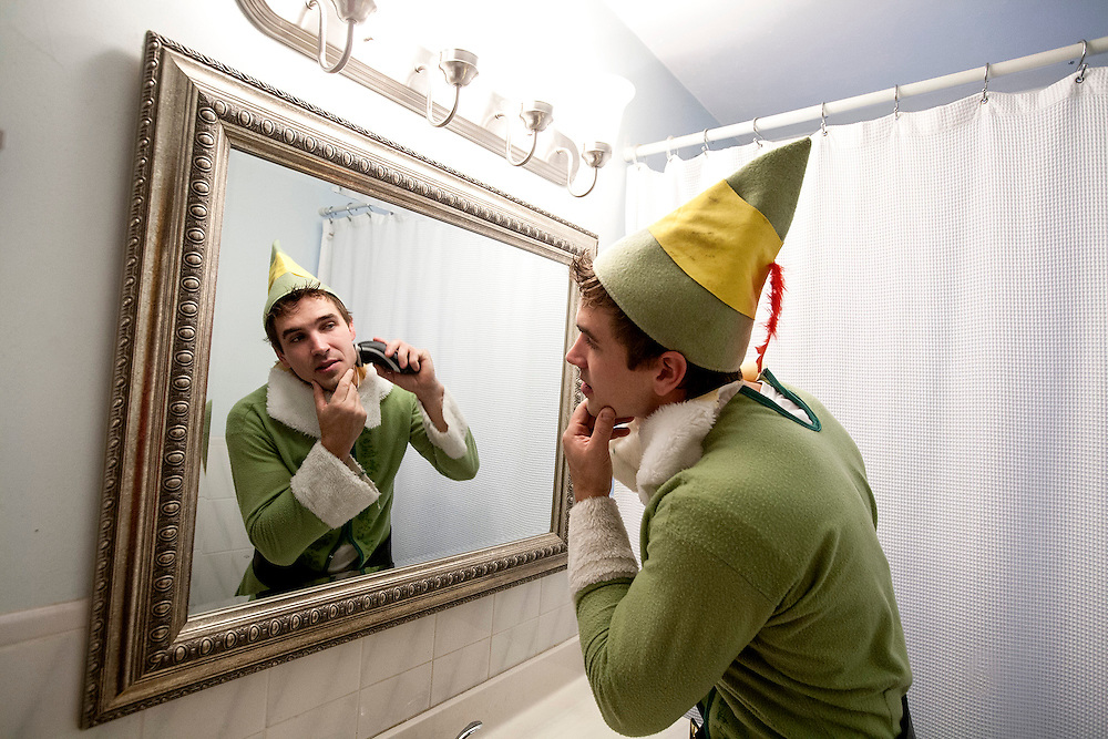"""Brandon Johnson, 29, shaves in preparation to work for his seasonal business, Santa's Tree Delivery, at his home in Northeast Minneapolis December 12, 2014.  """"Elves can't have stubble,"""" he said."""