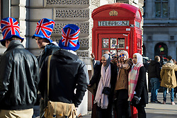 © Licensed to London News Pictures. 19/01/2016. London, UK. Tourists pose for photographs next to red phone boxes in  bright winter sunshine on Parliament square, central London. Photo credit: Ben Cawthra/LNP