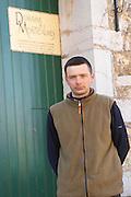 Vincent Guizard of Dom Saint Sylvestre in front of Domaine de Montcalmes in Puechabon. Terrasses de Larzac. Languedoc. A door. Owner winemaker. France. Europe.
