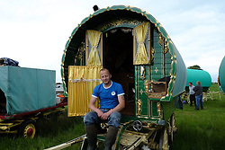 © Licensed to London News Pictures. <br /> 05/06/2014. <br /> <br /> Appleby, Cumbria, England<br /> <br /> Jason Plant from Stoke on Trent sits on the step of his bow top wagon as gypsies and travellers gather during the annual horse fair on 5 June, 2014 in Appleby, Cumbria. The event remains one of the largest and oldest events in Europe and gives the opportunity for travelling communities to meet friends, celebrate their music, folklore and to buy and sell horses.<br /> <br /> The event has existed under the protection of a charter granted by King James II in 1685 and it remains the most important event in the gypsy and traveller calendar.<br /> <br /> Photo credit : Ian Forsyth/LNP