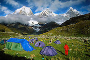 """Trekkers camp in tents in a green pasture at 13,600 feet elevation in the Cordillera Huayhuash, Andes Mountains, Peru, South America. Yerupaja Grande (left, east face, 6635 m or 21,770 ft) is the second-highest peak in Peru, highest in Cordillera Huayhuash, and highest point in the Amazon River watershed. At center is Yerupaja Chico (20,080 feet). On right is Mount Jirishanca (""""Icy Beak of the Hummingbird,"""" 6126 m or 20,098 feet). Up to 4 million copies of this image are agreed to be published in print and electronic media by Houghton Mifflin Harcourt (formerly Scholastic Inc) from 2009-2034 for the System 44 classroom paperback, """"Left to Die."""" Also published in """"Light Travel: Photography on the Go"""" book by Tom Dempsey 2009, 2010."""