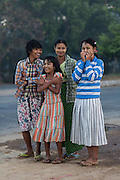 Family waiting for bus by side of road o cold morning, National Highway #1, Bago