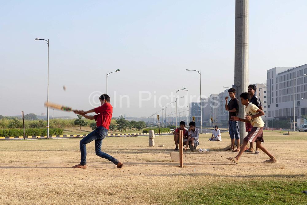 Boys play cricket on the private traffic greens at Aerocity near Terminal 3 of Indira Gandhi Airport, New Delhi, India