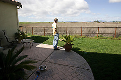 Homeowner  looks out on the wetlands behind his home during a break in packing.   The  Vallejo, Calif., couple ost their home in 2009 to foreclosure due to a combination of job loss, adjustable loan payments doubling and  home value under water nearly fifty percent. Photo by Kim Kulish