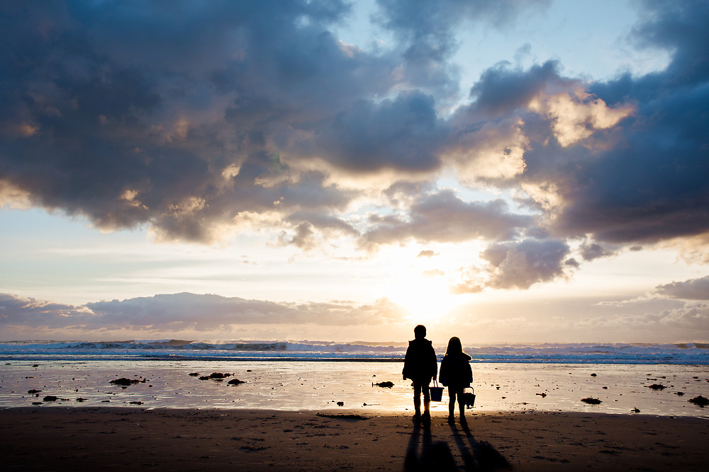 Two young children holding their buckets and watching the sun going down behind the sea at St Ouen's Bay in the Channel Islands