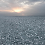 The sun sets behind clouds over the Arctic Ocean. Thin ice is beginning to form.