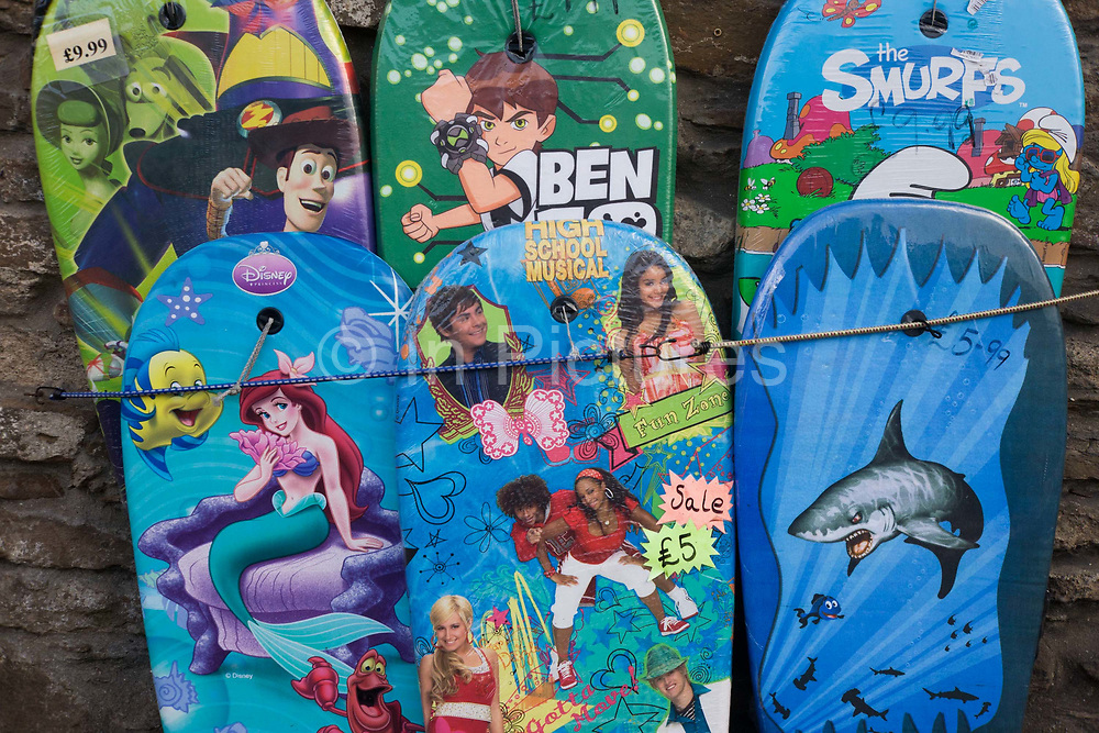 """Bodyboards on sale in the north Devon coastal village of Combe Martin. Various characters from the movie industry are represented on the top surfaces, attracting the younger buyer. The bodyboard differs from a surfboard in the fact that it is much shorter and made out of foam. Bodyboarding has been around since ancient Hawaiian days, it was called """"Paipo"""" and was made out of koa wood. The modern board consists of a foam 'core' encapsulated by a plastic bottom and a softer foam top known as the deck. The core is made up from dow/polyethylene, arcel or, more recently, polypropylene."""