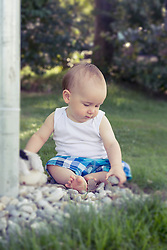 Baby boy playing with pebbles in lawn, Munich, Bavaria, Germany