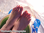 These are the feet of a beautiful redhead model shown her feet about to dip them in a bowl of green slime like cake batter.