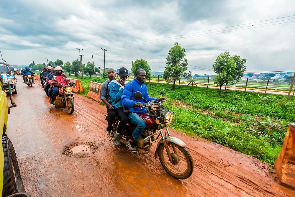 People riding three up on motorcycles, between Entebbe and Kampala, Uganda.