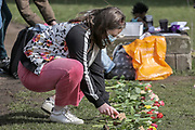 13th, March, 2021. Cheltenham. A member of the public lays out some flowers at the flower lay for Sarah Everard.