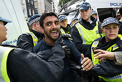 © Licensed to London News Pictures. 10/06/2018. London, UK. Police push a man back and away from a counter protest during the annual Al Quds day march in support of the Palestinian cause, in central London. Photo credit: Joel Goodman/LNP