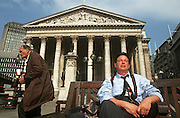 City workers enjoys lunchtime sunshine under solid Corinthian pillars of the 3rd Royal Exchange in City of London.