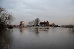 © Licensed to London News Pictures. 28/12/2015. Cawood, UK. A single property and the bridge at Cawood in North Yorkshire surrounded by flood water from the river Ouse, where flood water and rising tides have threatened the town. Several warnings of risk to life are sill in place in parts of Lancashire and Yorkshire where rainfall has been unusually high, causing heavy flooding. Photo credit: Ben Cawthra/LNP