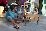 A man painting a chair in an antique shop, Vila Madalena neighbourhood, Sao Paulo, Brazil.