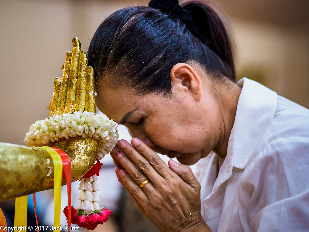 31 MAY 2017 - CHACHOENGSAO, THAILAND: A woman touches her head to the hand of a Buddha statue at Wat Sothon (also spelled Sothorn) in Chachoengsao, Thailand. The temple is one of the largest and most visited in Thailand. People make merit by paying to wrap the Buddha statues in orange robes. The temple is most famous because people leave hard boiled eggs as an offering at the temple. They ask for business success or children and leave hundreds of hard boiled eggs.      PHOTO BY JACK KURTZ