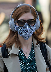 © Licensed to London News Pictures. 15/06/2020. London, UK. A commuter at Victoria Station in London wearing face masks, on the day the the easing of lockdown rules means all passengers must wear face masks. Government has introduced further measures to allow non-essential shops and services to reopen under social distancing conditions. Photo credit: Ben Cawthra/LNP