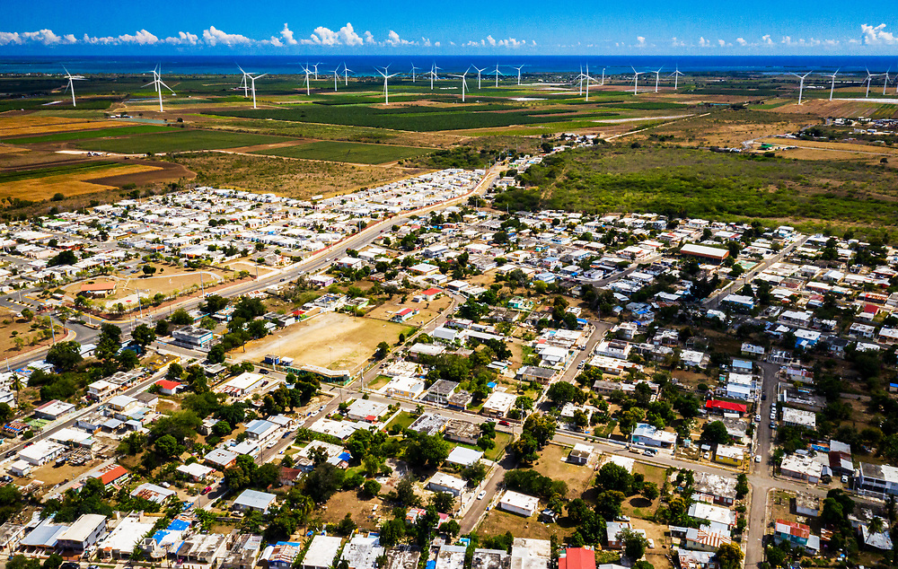 The town of El Ojo and the Santa Isabel Wind Farm. Could renewable energy help slow down the power and frequency of hurricanes for Puerto Rico? Many roofs blown off in Hurricane Maria in 2017 are still using blue tarps in 2020.