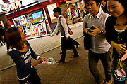 A young Japanese woman working as a restaurant tout tries to attract customers with fliers in Center Gai, now Basket Ball Street, in Shibuya, Tokyo, Japan Friday, September 4th 2009
