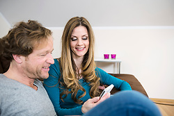 Smiling mature couple on couch with smartphone