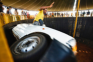 """Indian carnival workers small cars and motorcycles inside a """"wall of death"""" or motordrome at death defying speeds for paying spectators to watch in Pushkar, Rajasthan, India."""