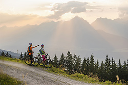 Young couple of mountain bikers standing on dirt road and looking at view during sunset, Zillertal, Tyrol, Austria