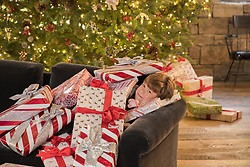 small boy underneath Christmas packages