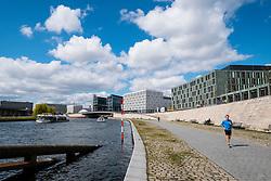View along riverbank walkway beside Spree River in Berlin Germany