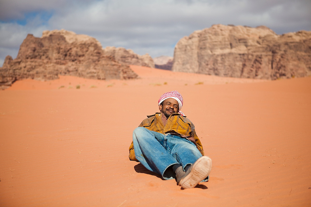 Sudanese Bedouin driver Ahmed relaxes on a sand dune in Wadi Rum, Jordan.