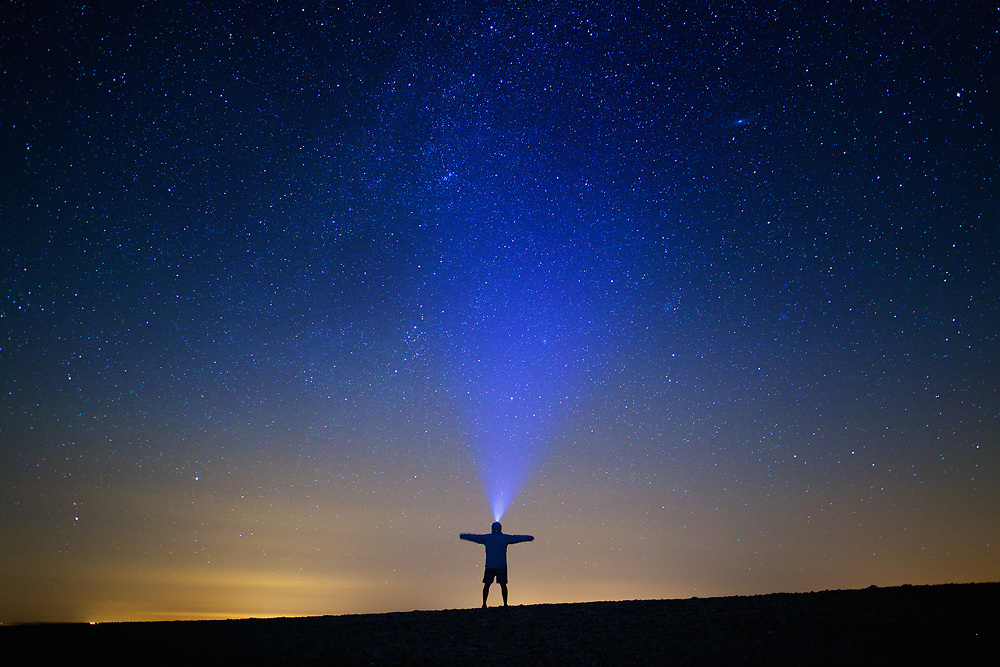 Man staring up at the starry sky on a clear night, at the tourist destination the Ecrehous, Jersey, Channel Islands