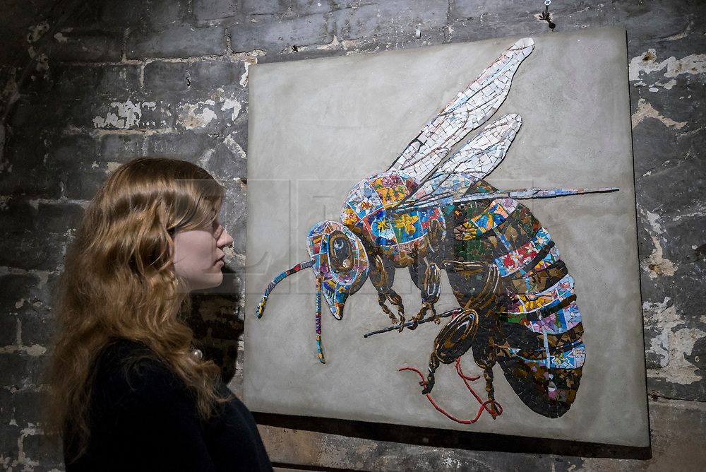"""© Licensed to London News Pictures. 24/05/2018. LONDON, UK. London, UK.  24 May 2018. An assistant views a mosaic of a bumble bee at the preview of """"Missing"""" an exhibition by artist and environmentalist Louis Masai at the Crypt Gallery in Euston.  The exhibition features sculptures, installations and paintings depicting 20 endangered species across the world from the South African penguin to the humble bumble bee.  The show runs 25 to 27 May 2018. Photo credit: Stephen Chung/LNP"""
