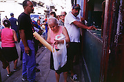 HAVANA, CUBA: People pick up their government ration of bread at a government bakery in the central section of Havana, Cuba. Many staples, like bread, rice and meat are still rationed in Cuba. Cubans make up for the lack of government rations by shopping in private farmers? markets and government run dollar stores.  Photo by Jack Kurtz