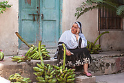 A woman chats on her cellphone, surrounded by her produce of green bananas on 6th December 2008 in Zanzibar, Tanzania. Zanzibar is a small island just off the coast of the Tanzanian mainland in the Indian Ocean. In part due to its name, Zanzibar is a travel destination of mystical reputation, known for its incredible sealife on its many reefs, the powder white coral sand beaches and the traditional cultivation of spices.