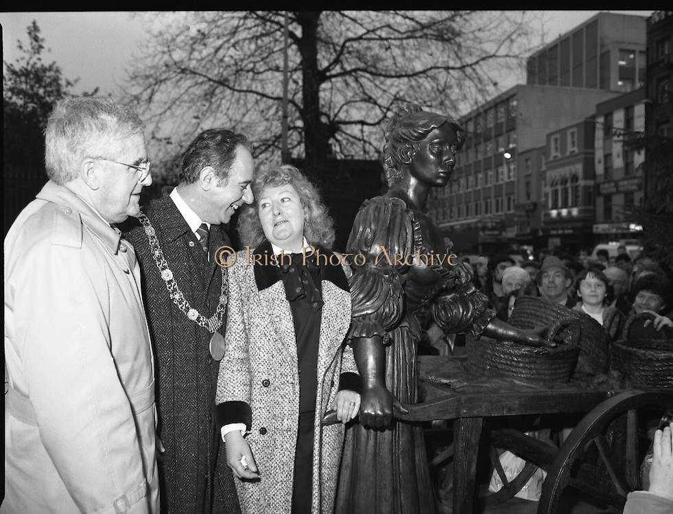 """Molly Malone Statue Unveiled. (R93)..1988..20.12.1988..12.20.1988..20th December 1988..""""Dublin's Fair City"""" received a millenniun gift to commemorate her most famous daughter, Molly Malone, when Jurys Hotel Group plc presented a specially commissioned sculpture to the people of Dublin. The sculpture was formally handed over by Michael McCarthy, MD,Jurys Hotel Group, to the Lord Mayor of Dublin, Councillor Ben Briscoe, TD, in an unveiling ceremony today at the corner of Grafton Street, Suffolk Street and Nassau Street..Molly Malone was created and fashioned in her traditional 17th century dress by Dublin born artist, Jeanne Rynhart, who was selected from a number of entries for the statue design, by the Dublin Millennium Board...In the shadow of the Christmas tree, Lord Mayor Ben Briscoe TD, Mr Michael McCarthy MD, Jurys Hotel Group and the artist Jeanne Rynhart are pictured at the official unveiling of """"Molly Malone""""."""