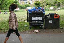 © Licensed to London News Pictures. 10/05/2020. London, UK. A woman walks past an overflowing bin in London Fields park in Hackney, north London today, following a tweet from local police reporting that hundreds of people were having pizzas, beers and wine on the hottest day of the year so far during lockdown on Saturday 9 May. Later today, Prime Minister Boris Johnson is set to announce measures to ease the coronavirus lockdown, which was introduced on 23 March to slow the spread of the COVID-19. Photo credit: Dinendra Haria/LNP
