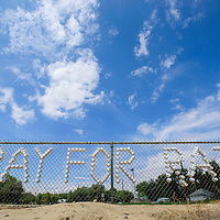 """082515       Cable Hoover<br /> <br /> A fence near the San Juan River bears the message """"Pray For Rain"""" in Shiprock Wednesday."""