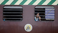 A woman watches the landscape pass her by on the Indian rails.