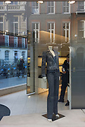 Three men use their smartphones in fifferent places of the street fashion shop, with a female's mannequin.