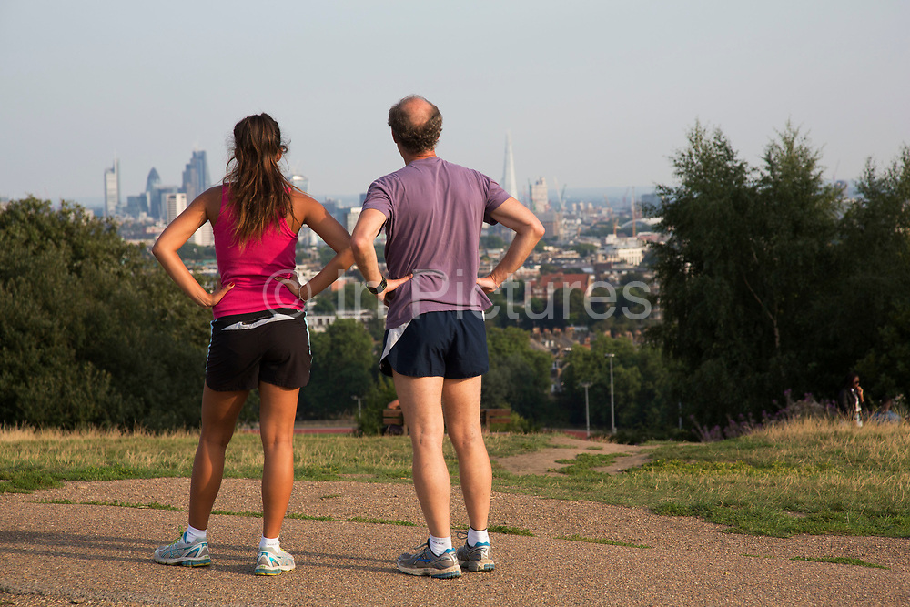 """Runners on top of Parliament Hill with an amazing view towards the City fof London. Hampstead Heath (locally known as """"the Heath"""") is a large, ancient London park, covering 320 hectares (790acres). This grassy public space is one of the highest points in London, running from Hampstead to Highgate. The Heath is rambling and hilly, embracing ponds, recent and ancient woodlands."""