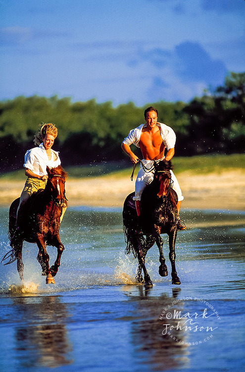 Couple riding horses on the beach ****Model Release available