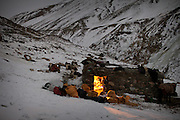 Kyrgyz men seek shelter in a shepherd's hut during the icy five-day trek down from their mountainous homeland to the nearest trading village in Afghanistan. They will barter livestock, wool, and dairy products for everything from tea to television sets...In Zan Kuk. .Trekking back down from the Little Pamir, with yak caravan, over the frozen Wakhan river.