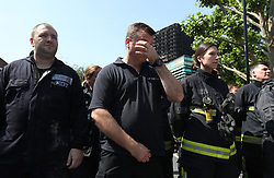 Members of the police and London Fire Brigade observe a minute's silence near to Grenfell Tower (background) in west London after a fire engulfed the 24-storey building on Wednesday morning.