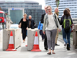 Commuters make their way past concrete barriers on Westminster Bridge in London which have been placed there overnight following Saturday's terrorist attack.