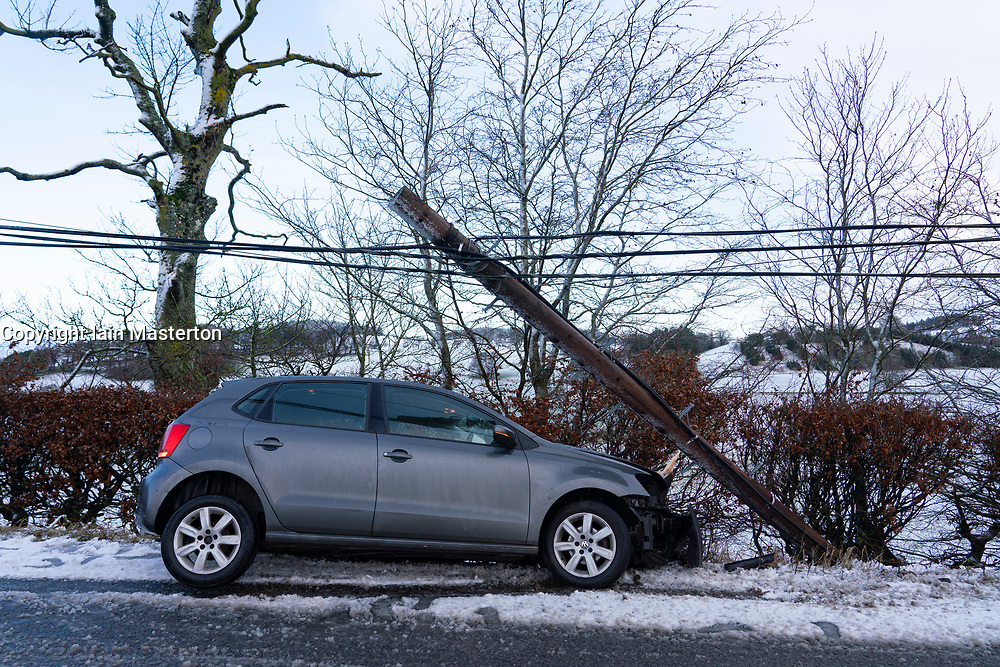 Blyth Bridge, Scotland, UK. 27 December 2020. Road traffic accident caused by snow and ice on the road on the A72 near Blyth Bridge, West Linton. The car completely severed a timber telegraph pole. No occupants were injured.  Iain Masterton/Alamy Live News