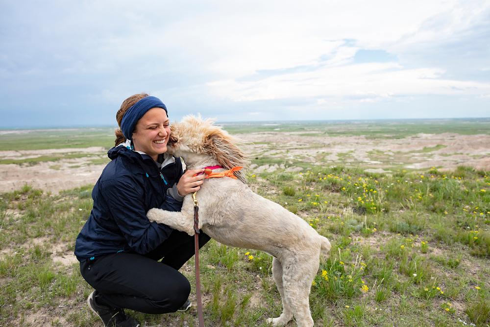 dog kissing young woman