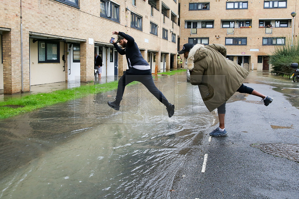 © Licensed to London News Pictures. 08/10/2019. London, UK. Residents are seen leaping over water in Theobalds Court following a burst water main on Brownswood Road in Finsbury Park, north London. Photo credit: Dinendra Haria/LNP