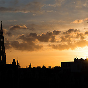 The silhouette of Brussels skyline at sunset against a golden sky with a few clouds. The tall spire is the tower of the Brussels Town Hall (Hotel de Ville) standing at 96 meters.
