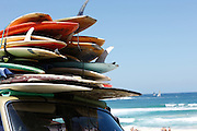 surfboards stacked up high on a car roof at bondi beach. from colour (color) photo series by award winning photographer Paul Green.Sunny Summer Day, sailing yachts out at sea.