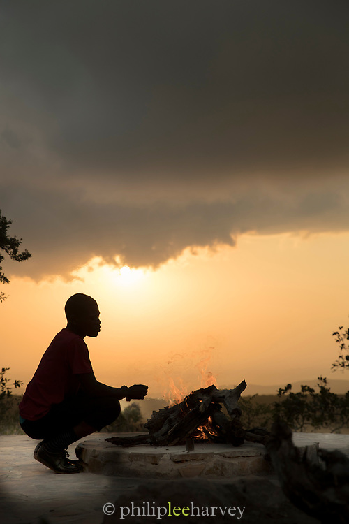 Silhouette of staff member squatting by camp fireside at dusk, Mhlumeni Bush Camp, Eswatini